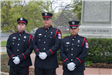 Three Honor Guard Members Stand Beside a Statue