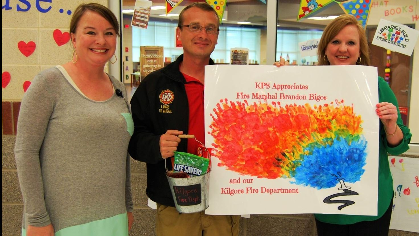 Brandon Bigos pictured with the Kilgore Primary School librarian and assistant principal.