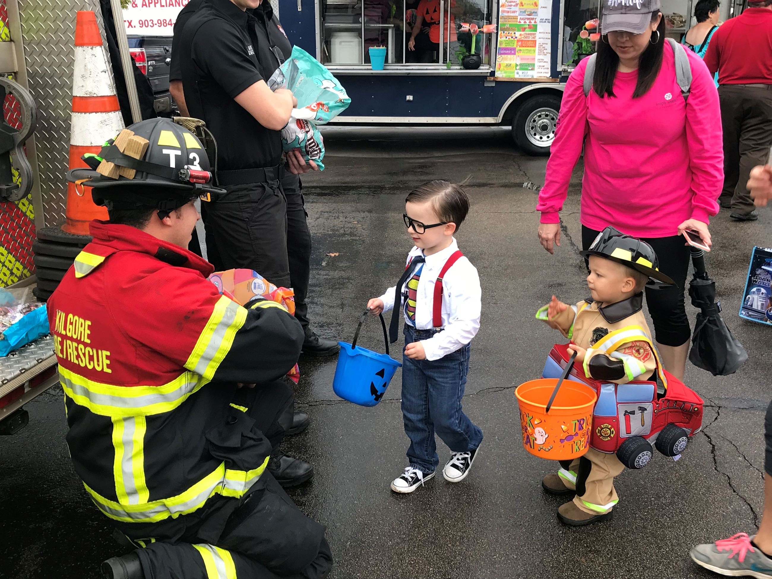Young children dressed up for Trick or Treat receiving candy from a firefighter