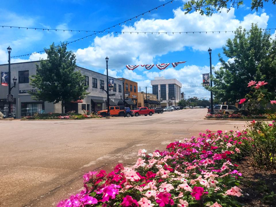 Downtown Kilgore featuring the flower beds, patriotic flags flying and streetscapes.