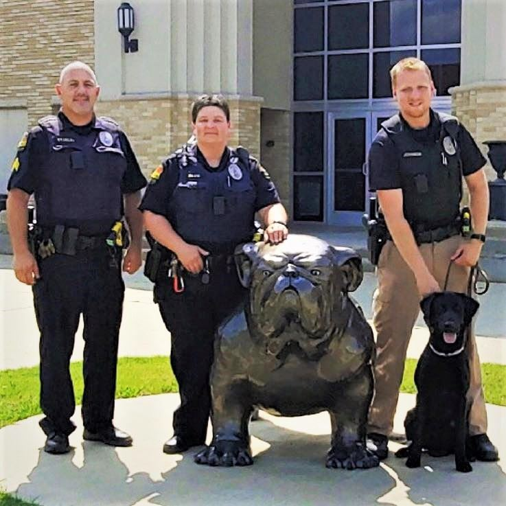 3 School Resource Officers and K9 Ruger standing by Bulldog statue