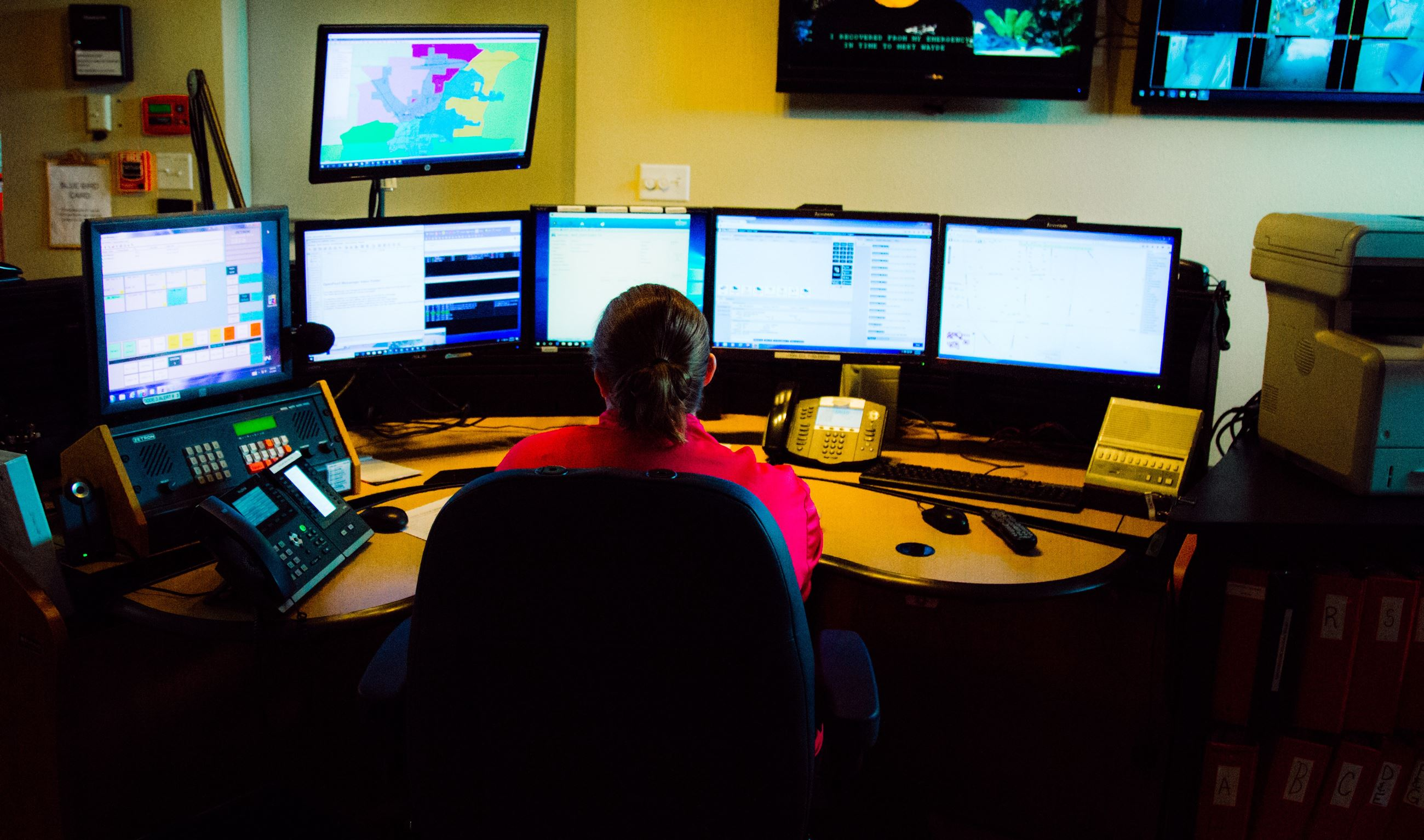 Dispatcher looking at multiple computer monitors in dispatch center, 911, 9-1-1, communications
