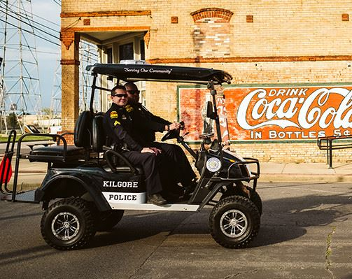 Two policemen riding in a golf cart in front of a Coca-Cola sign
